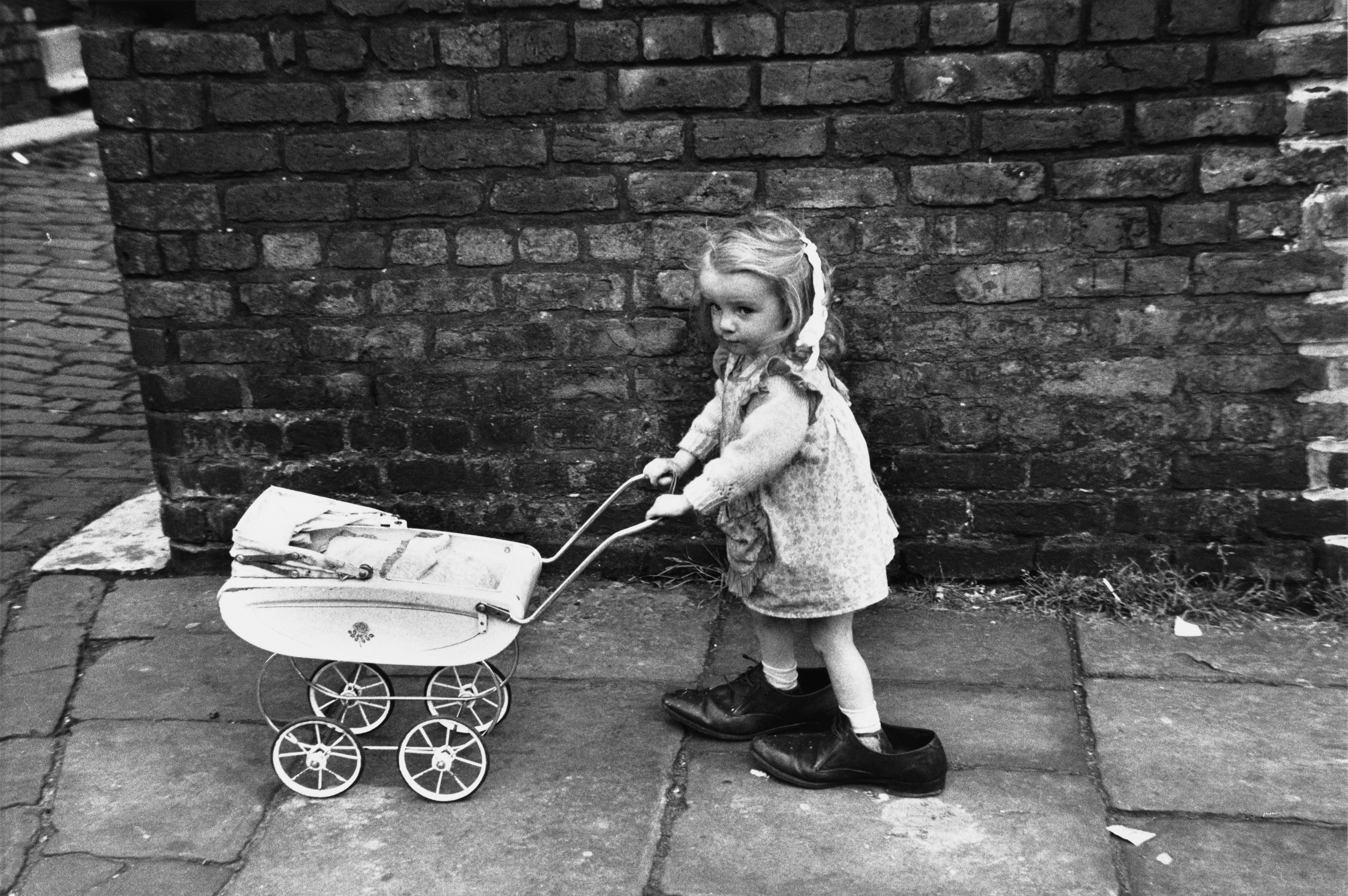 Little Girl with Toy Pram in Large Shoes, Manchester 1966. Photograph by Shirley Baker (1932-2014)